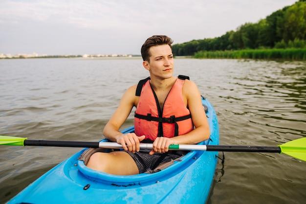 Macho, sentando, em, kayak, segurando, pá, olhando