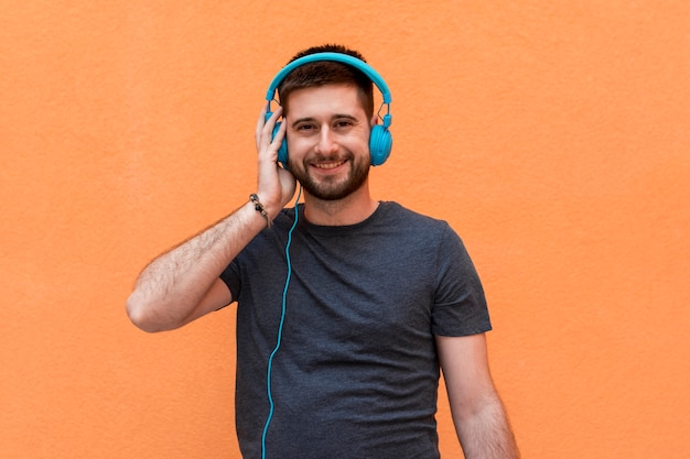 Macho sorridente com fones de ouvido azuis