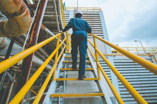 Macho subindo a escada visual de inspeção na fábrica