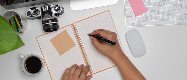 Macho tomando nota no caderno em branco na mesa de escritório