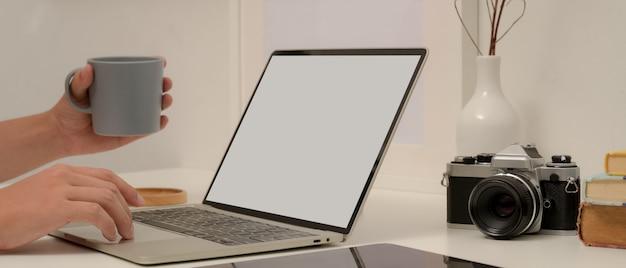 Macho trabalhando com mock up laptop, mantendo a xícara de café na mesa de trabalho moderna no escritório em casa