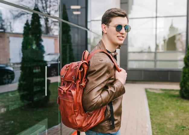 Macho usando óculos escuros modelo mochileiros viajam férias de viajante na cidade.
