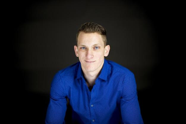 Macho vestindo uma camiseta azul e sorrindo para a câmera com uma parede preta