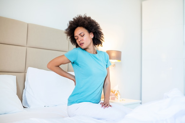 Machucar jovem americana africano sente-se na cama branca acorda toque volta sofrendo de dor nas costas dolorosa