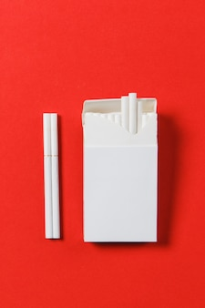 Maço de cigarros branco sobre fundo vermelho