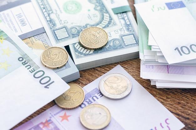 Maço de notas de dólar e euro com moedas