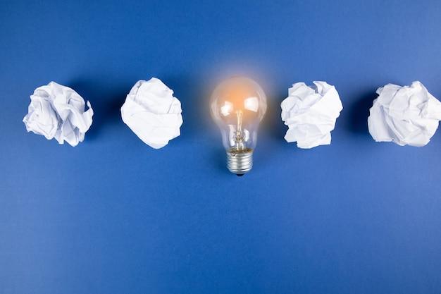 Maço de papel e lâmpada na superfície azul