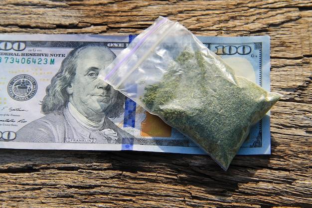 Maconha em pacote e nota de 100 dólares na mesa de madeira