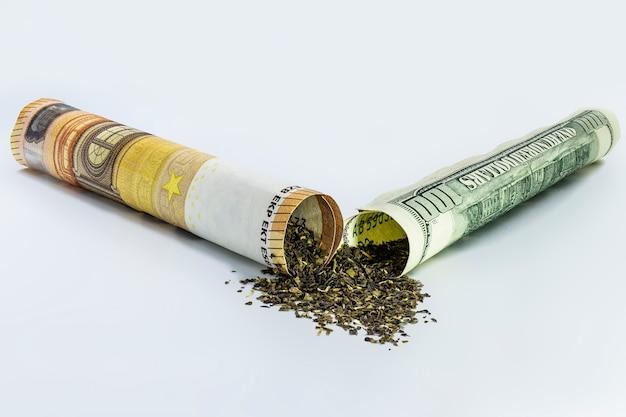 Maconha em uma nota de cinquenta euros e uma nota de cem dólares em forma de cigarro. conceito de negócio de cannabis. maconha e dinheiro. drogas.