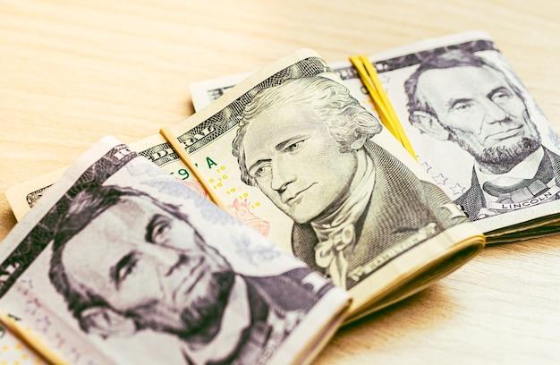 Maços de notas dobradas de dólares americanos em uma mesa de madeira em fotografia de close