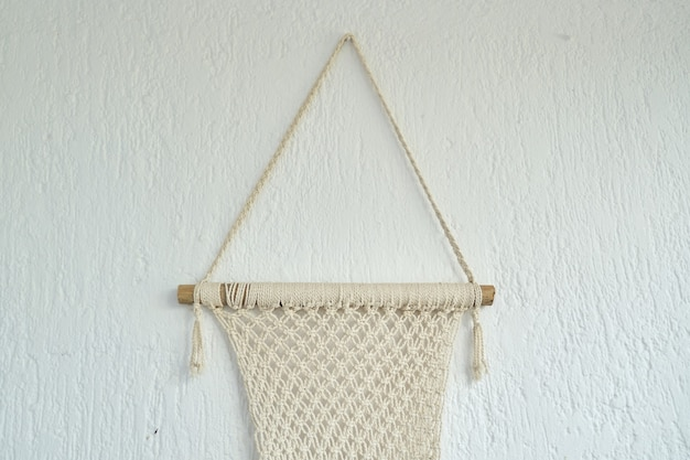 Macramê artesanal, painel decorativo tecido com leves cordas de algodão na parede.