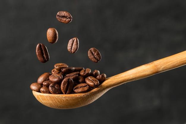 Macro caindo feijão de café sobre fundo cinzento