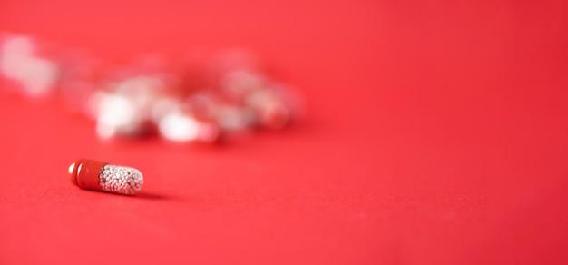 Macro de cápsulas vermelhas sobre fundo vermelho. copie o espaço. grupo de drogas, tratamento da gripe fria.