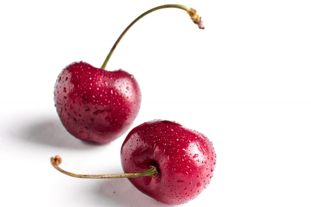 Macro de duas bagas de cereja vermelha com gotas de água no fundo branco