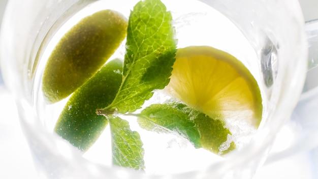 Macro de folhas de hortelã, cubos de gelo e rodelas de limão flutuando em um copo de limonada.