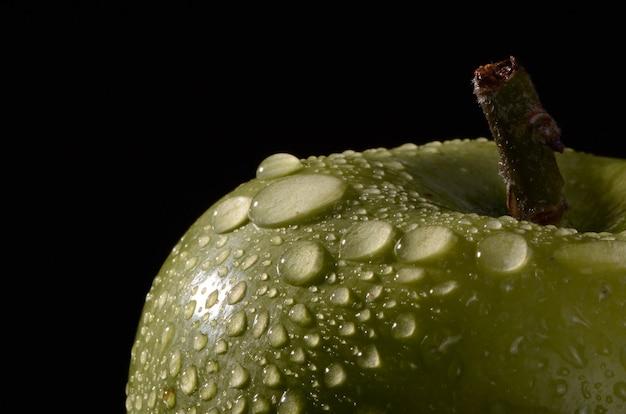 Macro de maçãs verdes recentemente colhidas com gotas de água.