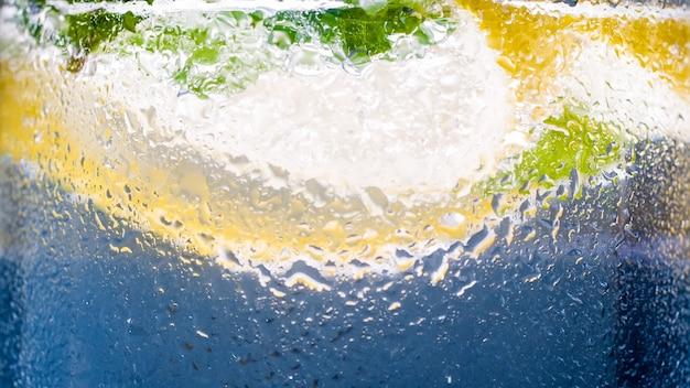 Macro de vidro frio enevoado com limonada de limão e gelo.