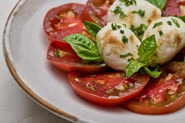 Macro deliciosa salada caprese com tomate vermelho, manjericão fresco e mussarela com foco seletivo