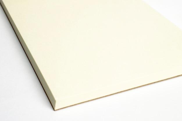 Macro do canto do caderno aberto em branco com capa dura de papelão isolada