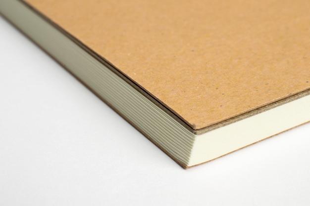 Macro do canto do caderno em branco com capa dura de papelão isolada no branco