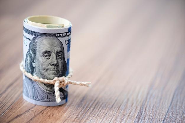Macro do rolo de notas de 100 dólares americanos no espaço de madeira de fundo e cópia