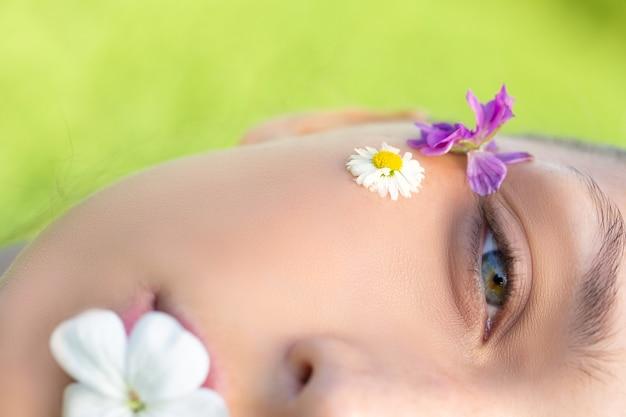 Macro fotografou metade do rosto bonito de uma mulher com flores silvestres