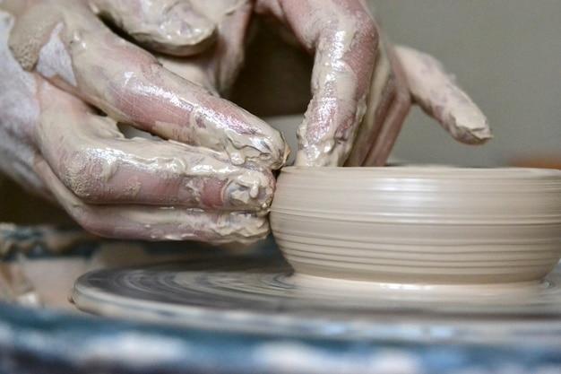 Macro, o oleiro faz panela de barro, mãos fazendo prato de barro