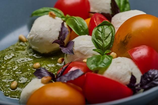 Macro tradicional salada caprese com tomates maduros, pinhões, manjericão e queijo mussarela em cinza