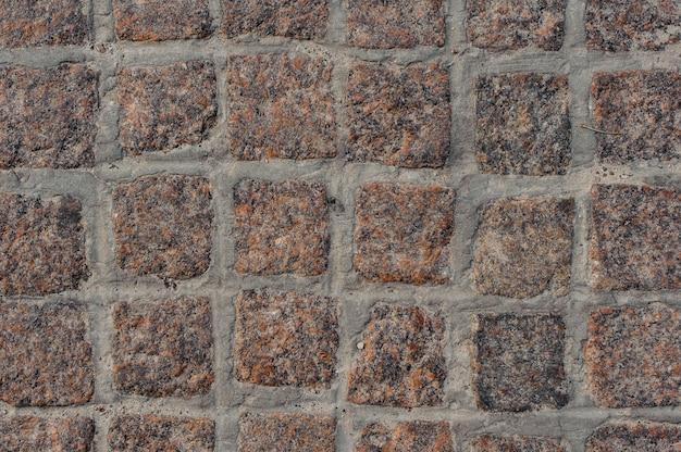 Macrofotografia de fundo superior do pavimento de estrada de bloco de pedra marrom