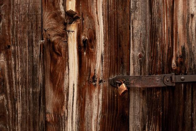 Madeira antiga com superfície desgastada e dobradiça e fechadura de metal