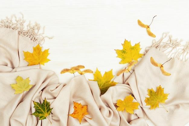 Madeira branca com estação seca outonal amarela folhas de ácer, cachecol têxtil aconchegante. copie o espaço. vista do topo.
