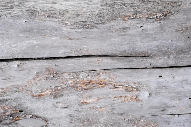 Madeira compensada cinzenta rachada, fundo de madeira velho da textura. papel sujo, moldura de madeira vintage. chão gasto, tábua arranhada. parede do grunge. Foto Premium