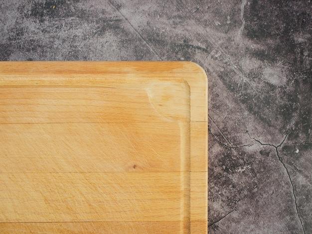 Madeira da placa de corte na mesa de mármore cinza.