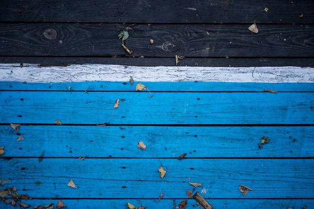 Madeira escura de madeira vintage, metade pintada de azul.