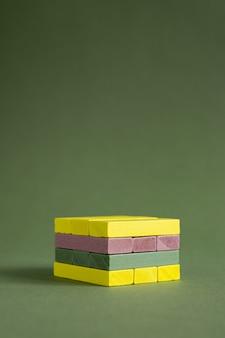 Madeira jenga colorida verde e amarelo sobre fundo verde cópia espaço plataforma para produto