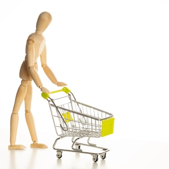 Madeira manequim de compras com carrinho. isolado no fundo branco.