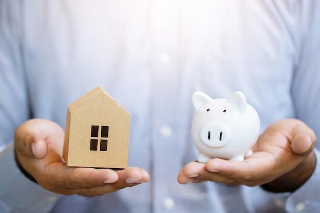 Madeira modelo para casa na mão do homem segurando salvando a pequena casa com um telhado. conceito de crise de parcela ou empréstimo e hipoteca do negócio.