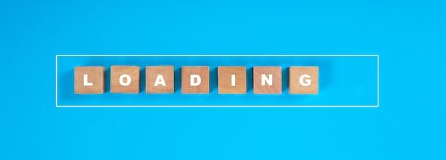 Madeira quadrada com barra de carregando letras em andamento sobre um fundo azul.