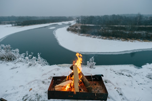 Madeira queimando na churrasqueira no chão nevado no rio. paisagem do inverno com churrasco e rio.