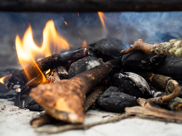 Madeiras ardentes em local de fogueira com fumaça