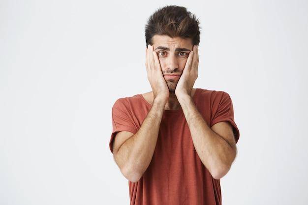 Madura cara caucasiano atraente em camiseta vermelha e penteado na moda, segurando o rosto com as mãos chateadas com grande quantidade de trabalho.