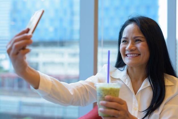 Madura linda empresária asiática relaxante dentro do café