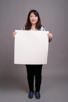 Madura linda empresária asiática segurando um cartaz em branco