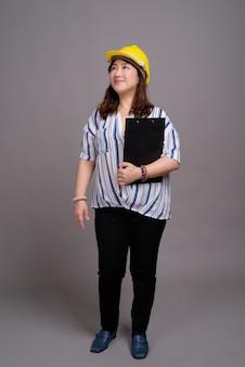 Madura linda empresária asiática usando capacete de segurança