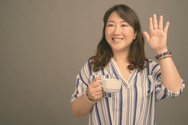 Madura linda mulher asiática em cinza