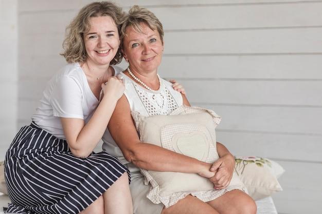 Madura mãe sorridente segurando almofada sentado com sua linda filha