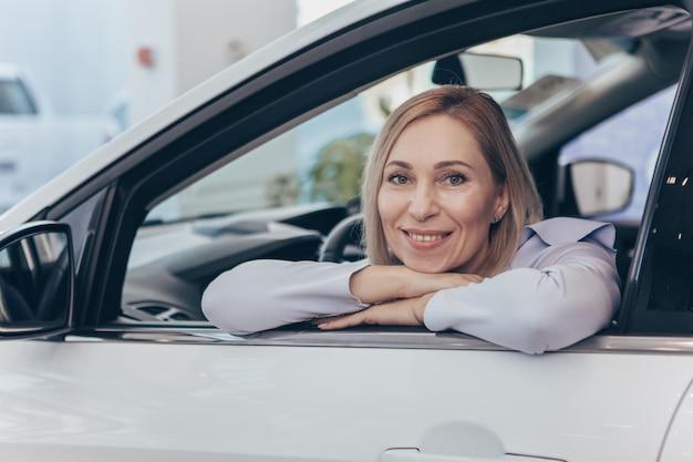 Madura mulher alegre, sentado em um automóvel novo no salão da concessionária