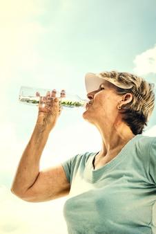 Madura mulher ativa bebendo um pouco de água