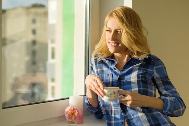 Madura mulher loira bonita olha pela janela