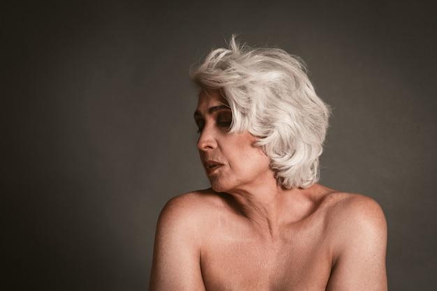 Madura mulher nua em fundo cinza